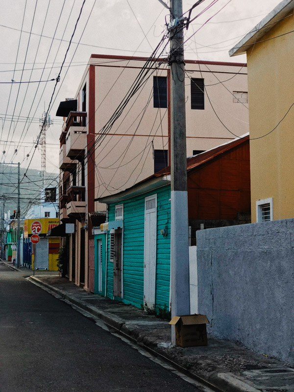 A street in the Dominican Republic showing a row of colourful shops and homes and telephone lines taking over the sky