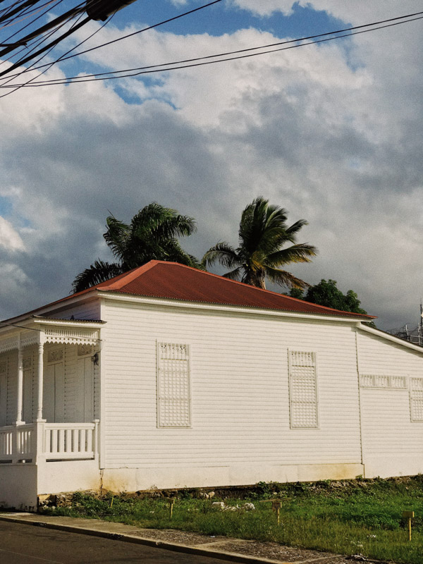 A white house with a terracotta roof, with palm trees moving in the wind in the background in the Dominican Republic