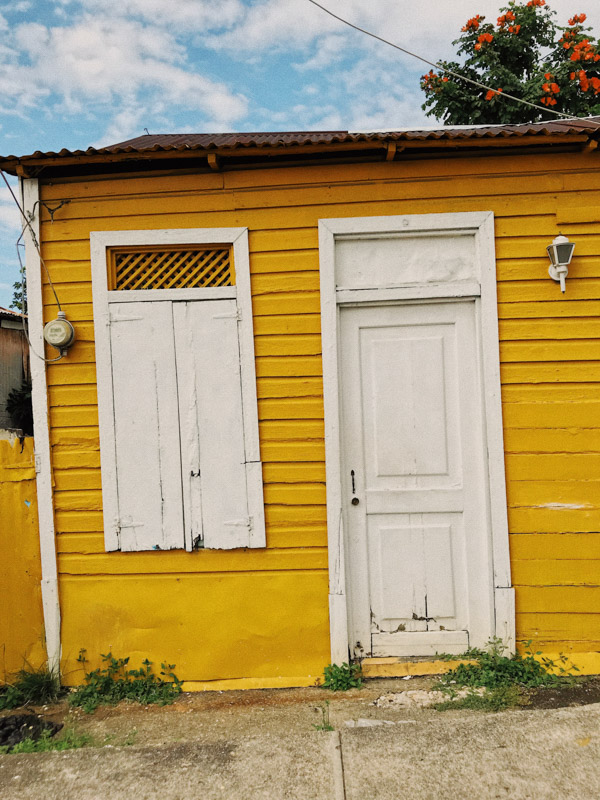 The front of a yellow house in the Dominican Republic, with a white door and one white window