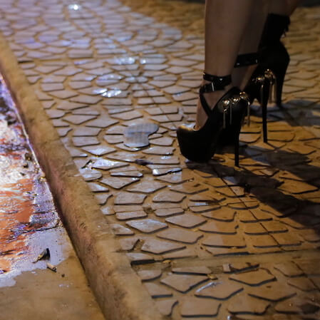 A women standing outside a bar in heels