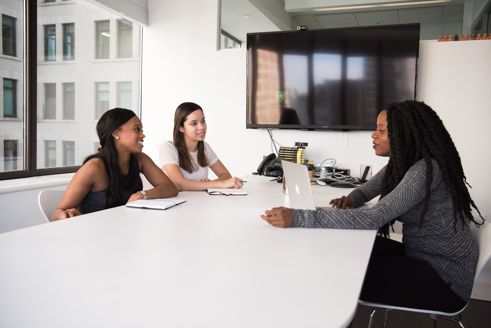 A hiring manager sitting at a table with two prospective internal hires
