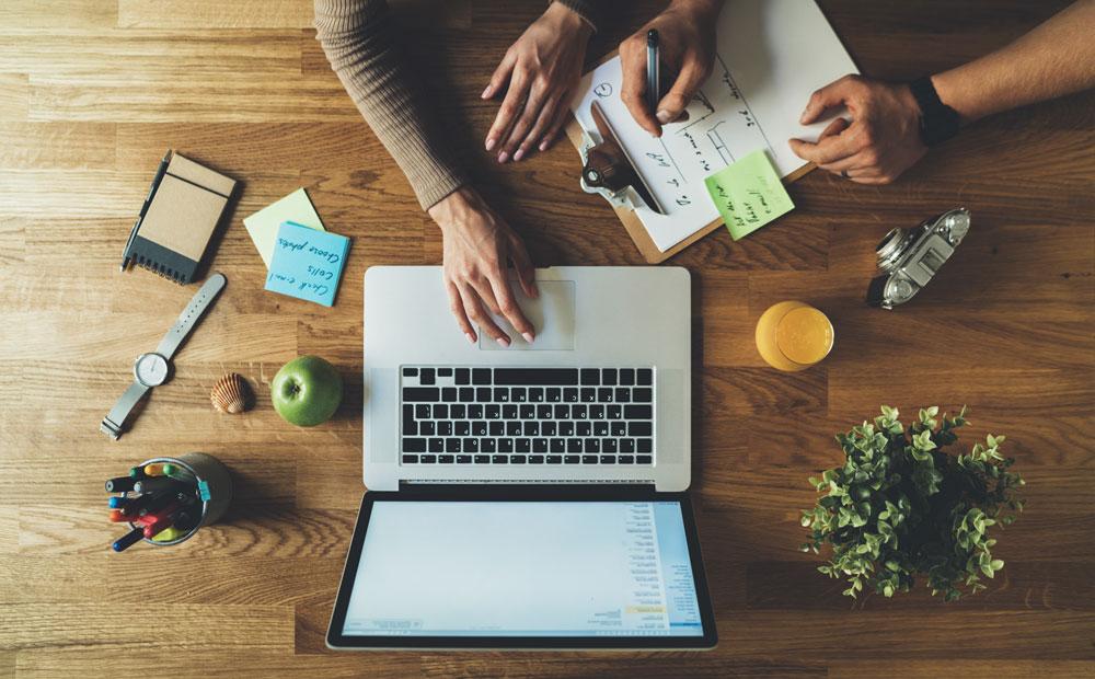 Dva lidé, před kterými je otevřený notebook a také seznam různých úkolů, které si postupně odškrtávají.