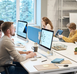 Showing three people in a shared working environment working with computers.