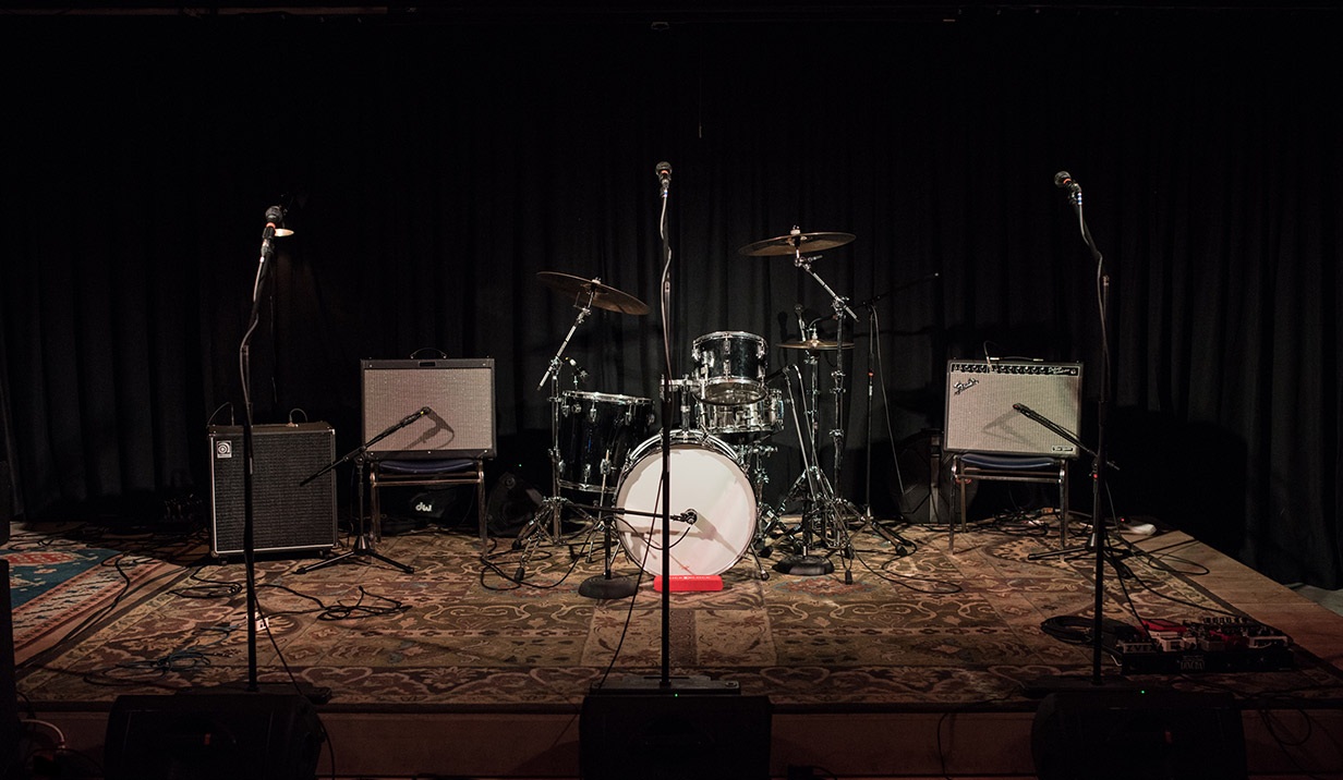 Stage with black backdrop and drum set and amplifiers and microphones.