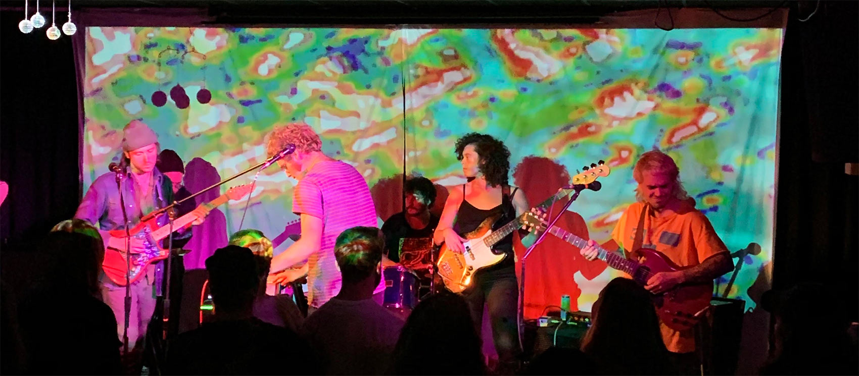 Stage with live band and colorful backdrop. Band is Carinae from Western Massachusetts.