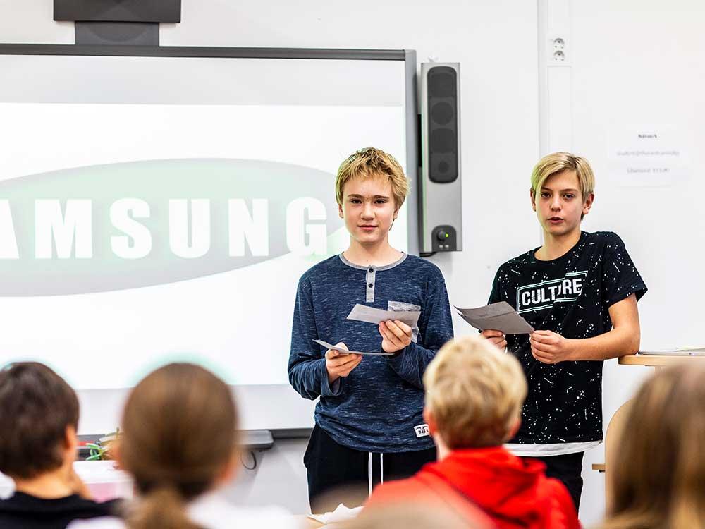Två elever som presenterar för klassen framför en smartboard