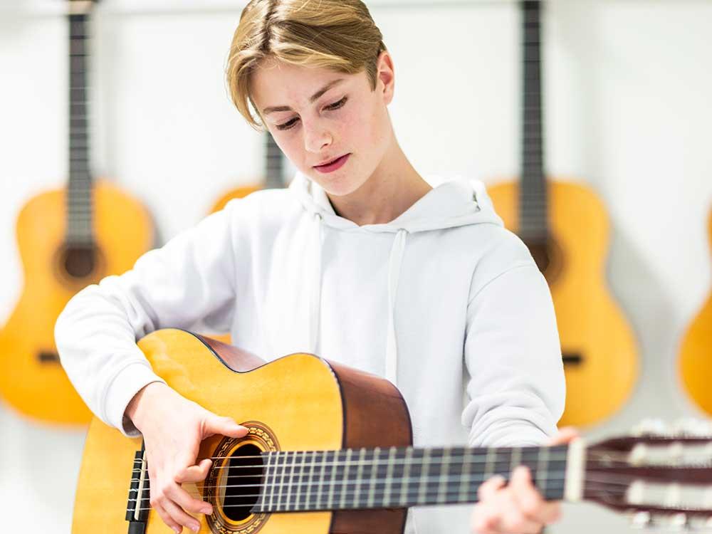 En elev som spelar gitarr