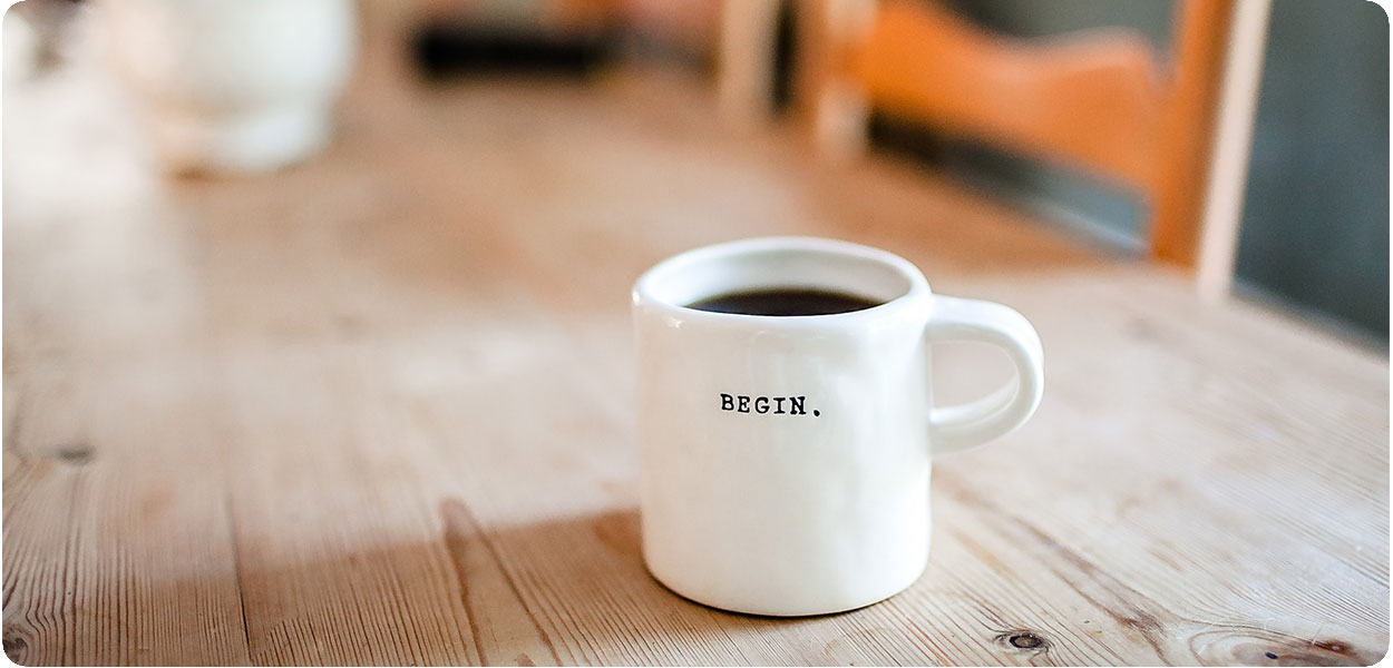 a cup of coffee that says begin on it which shows how to start a business.