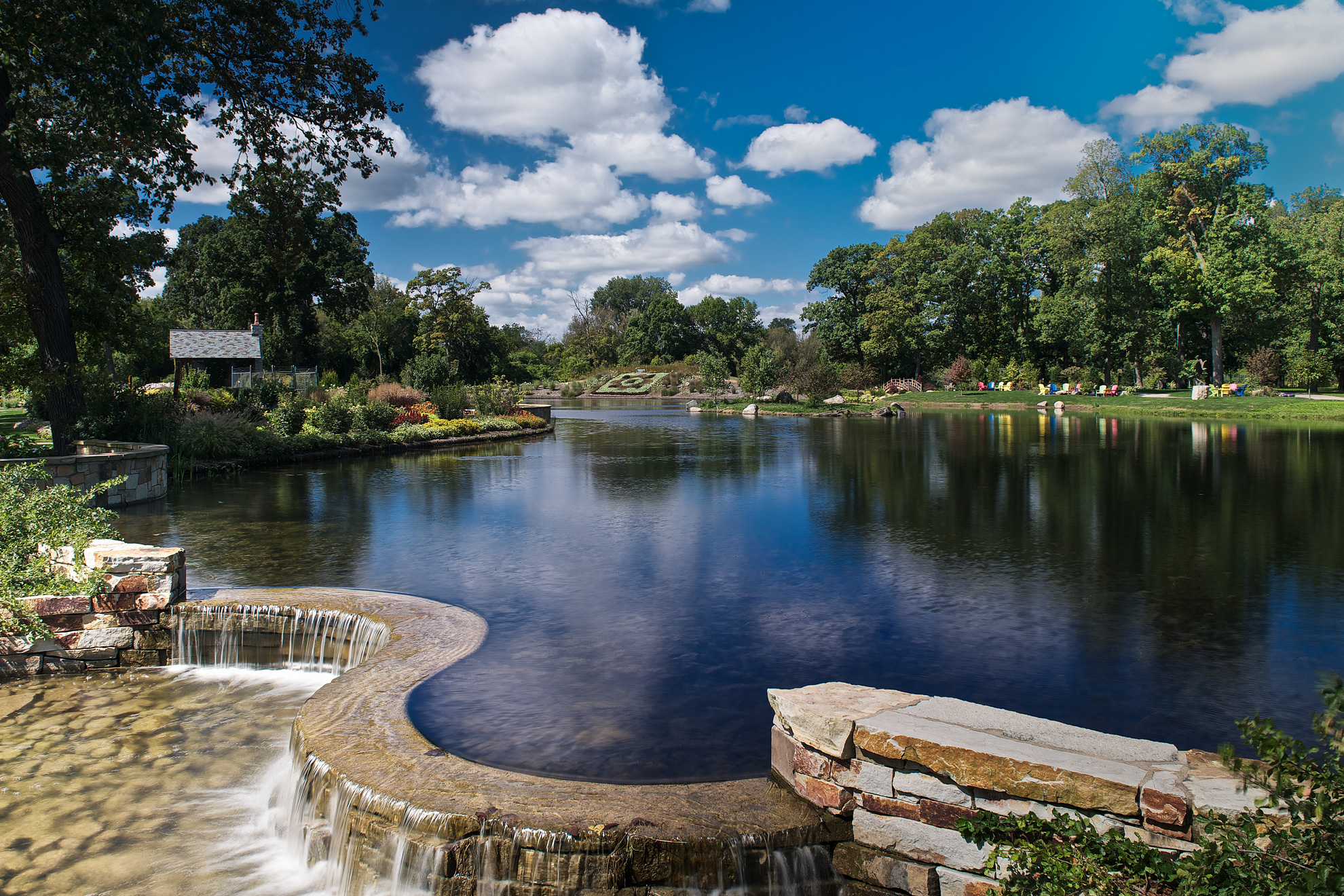 A beautiful waterfall over lookin the large pond at Wellfield Botanic Gardens in Elkhart Indiana designed by JPR