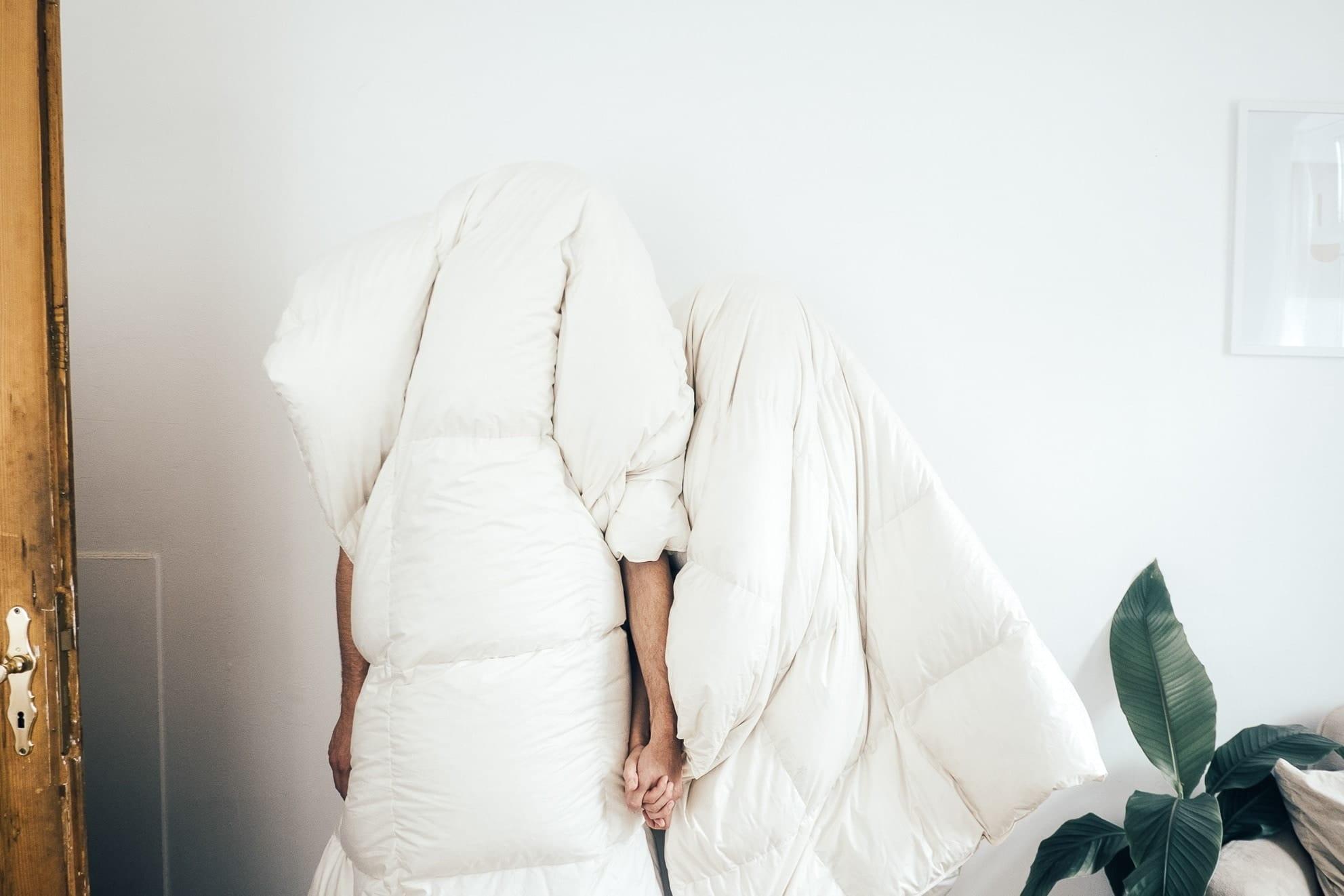 Zwei Personen haben jeweils eine Decke über den Kopf, die den gesamten Körper verdeckt und halten Hände