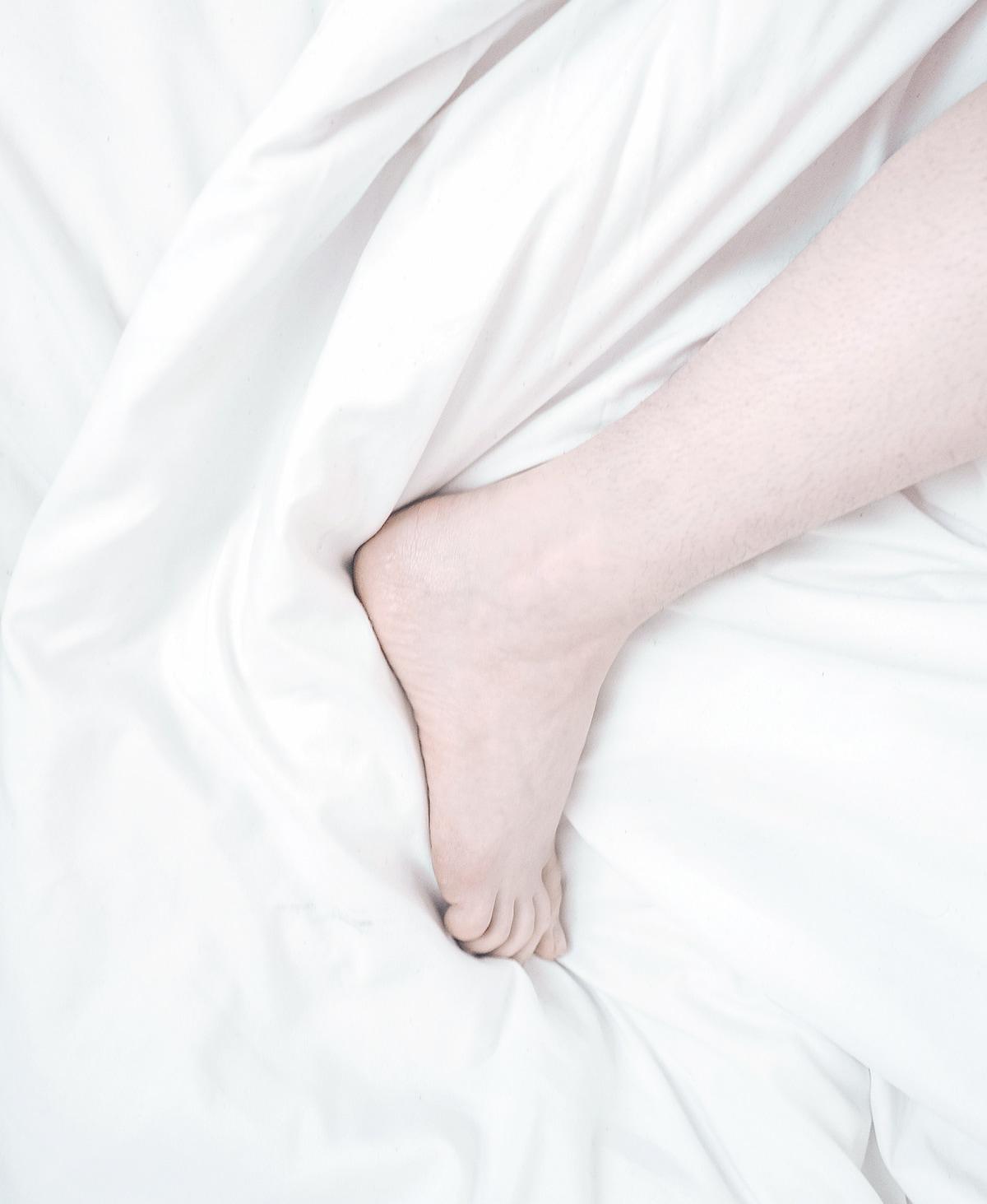 Fuß und Bein auf Daunendecke mit weißer Bettwäsche