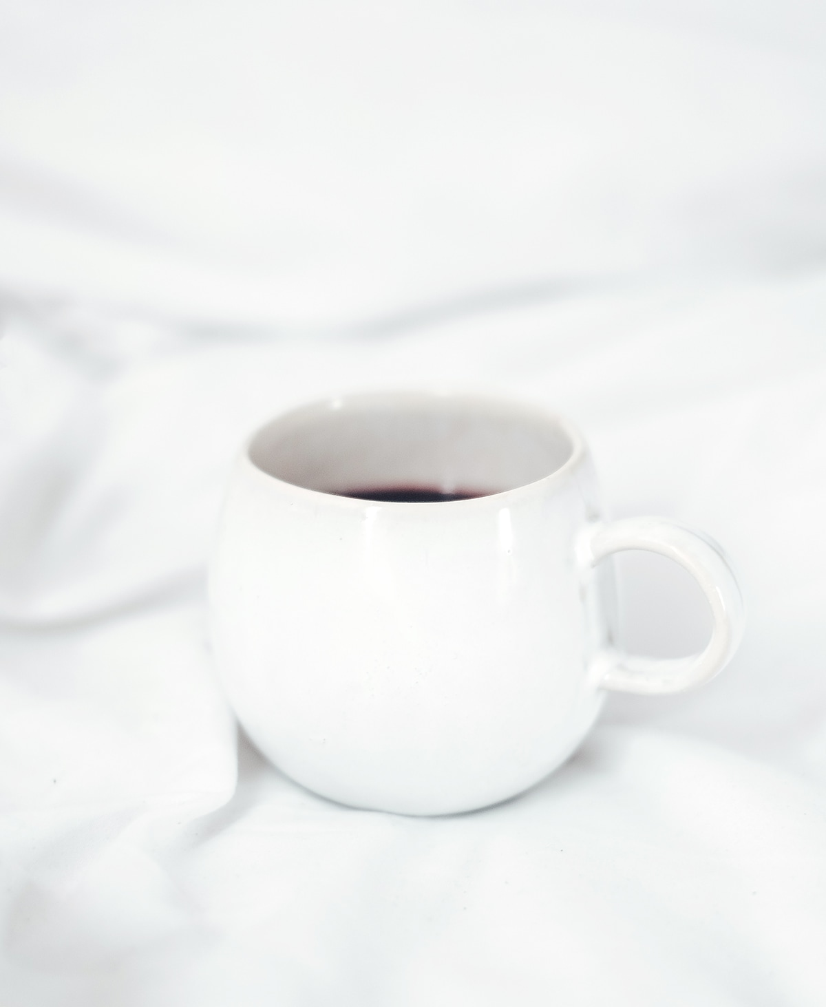weiße Tasse mit Kaffee gefüllt auf einem Bett mit weißer Bettwäsche