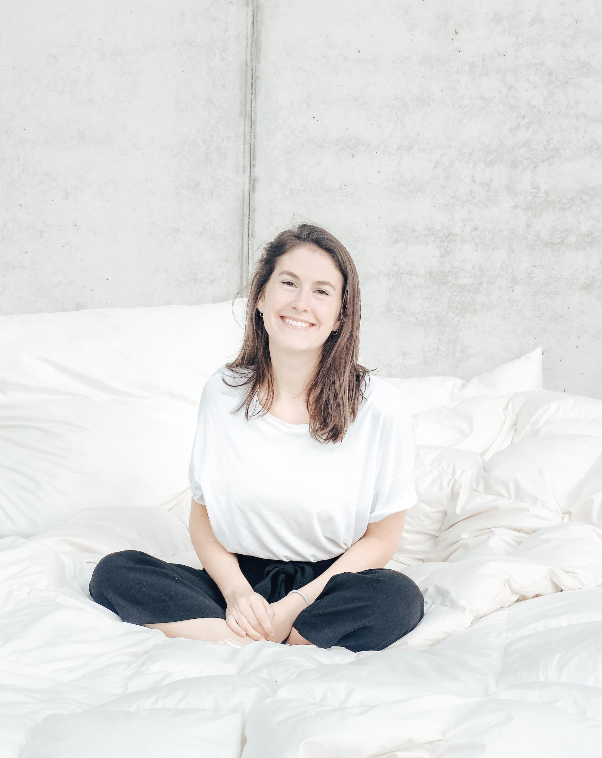 Gründerin Frederike sitzt im Schneidersitz auf einem Bett