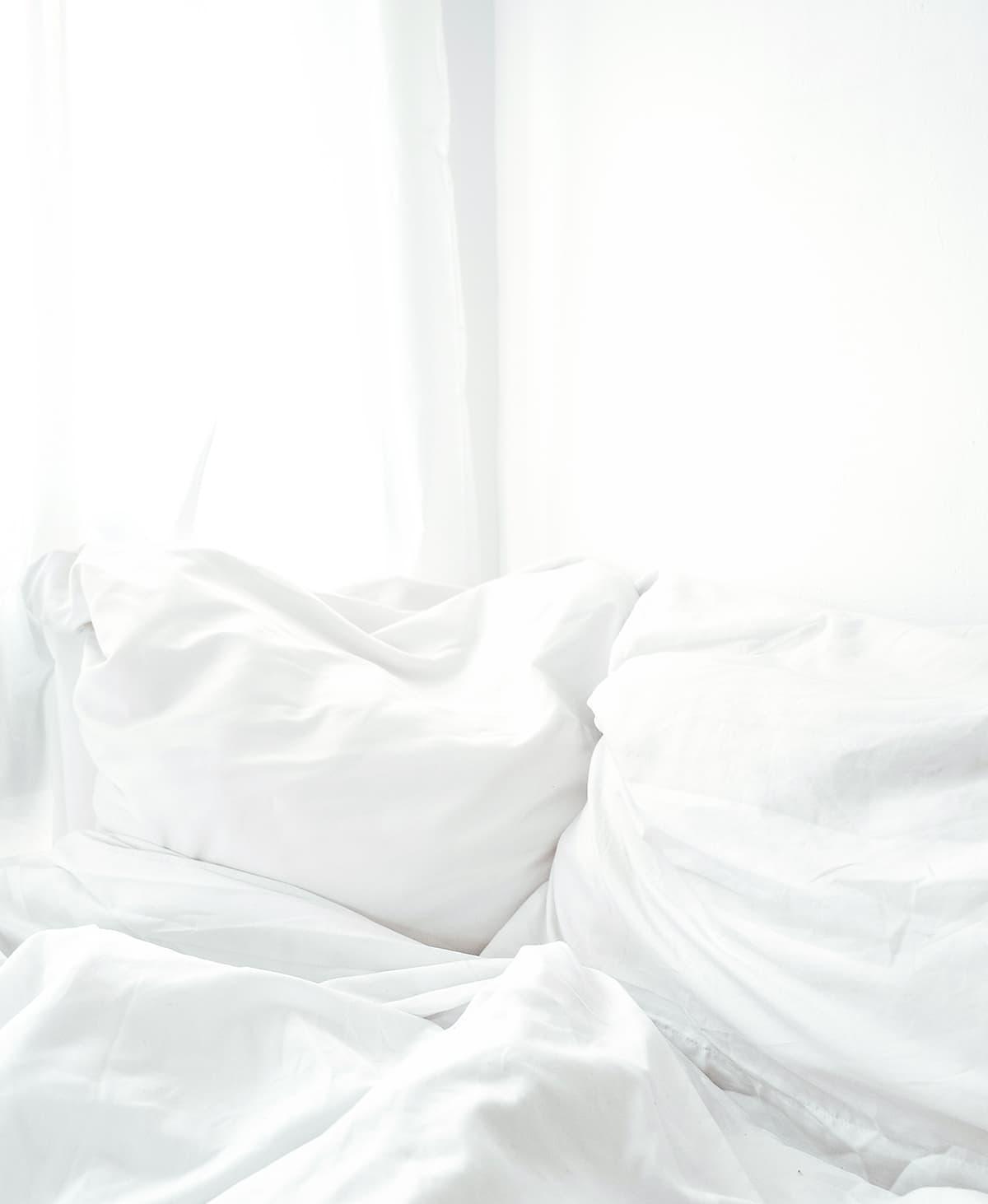 Daunendecke und Federkissen in weißer Bettwäsche vor weißer Wand