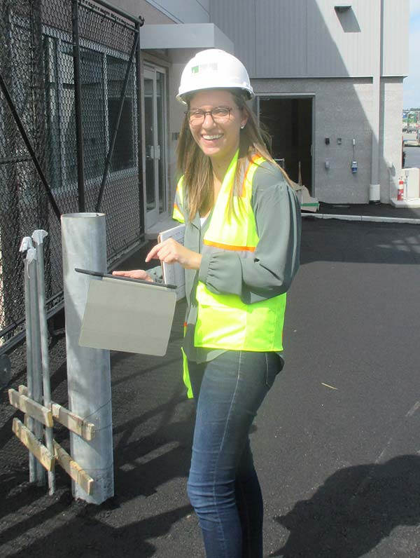 Cori on site wearing a hard hat and neon vest.