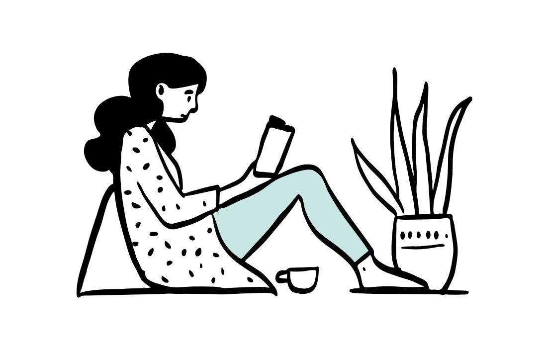 Schülerin sitzt am Boden und lernt aus einem Buch