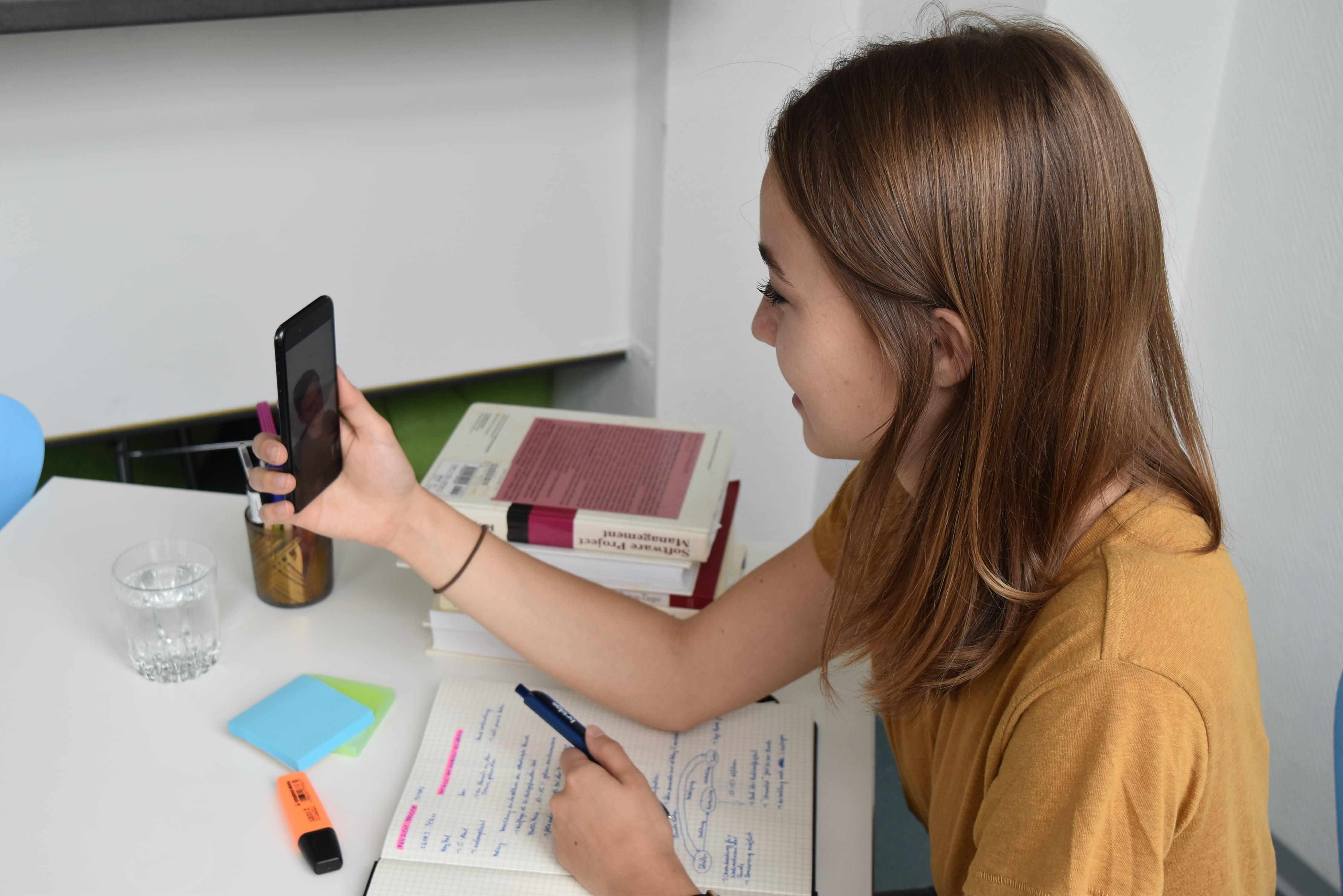 Mädchen spricht mit Nachhilfeleher*in über das Smartphone