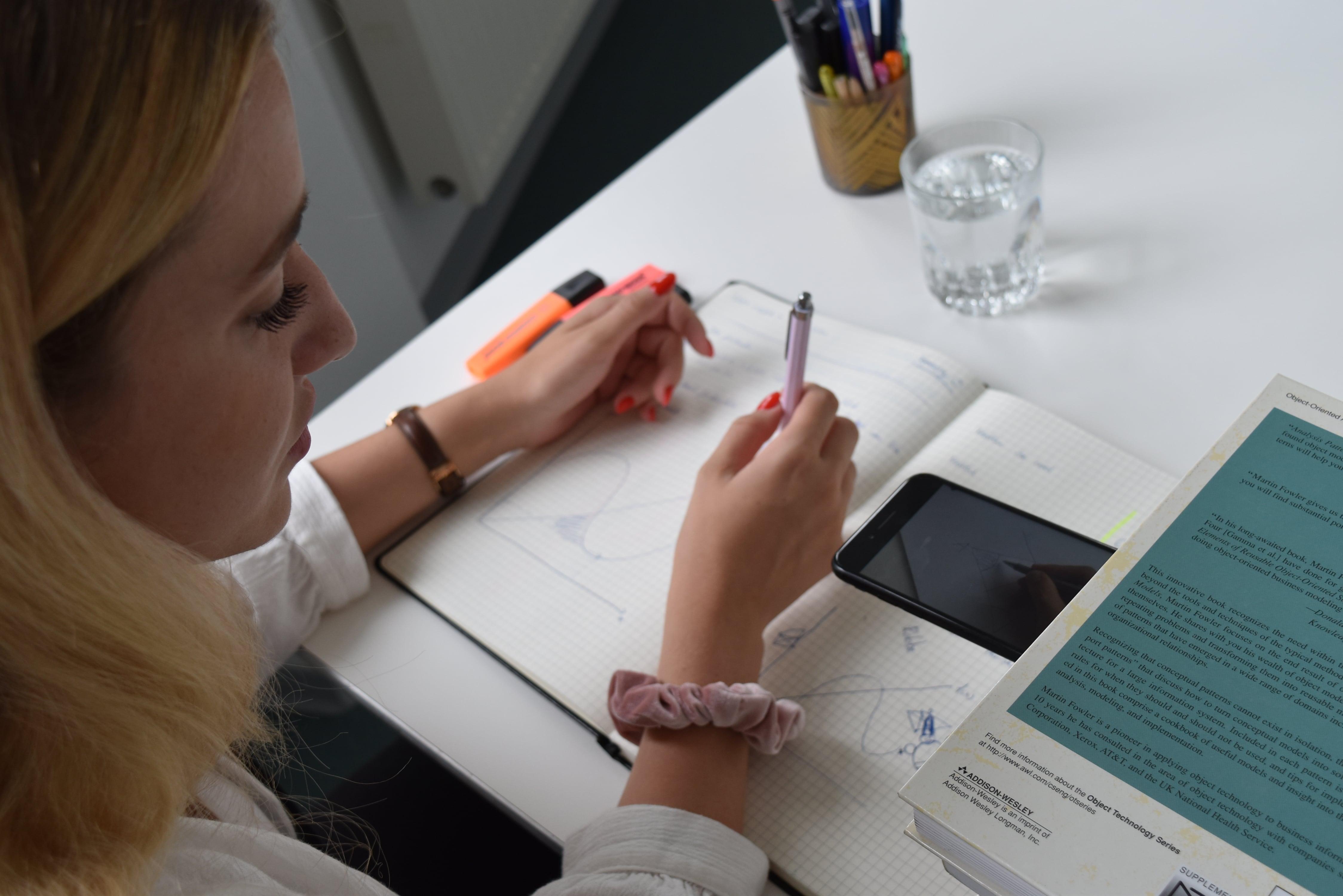 Schülerin sitzt an einem Tisch und lernt mit dem Smartphone