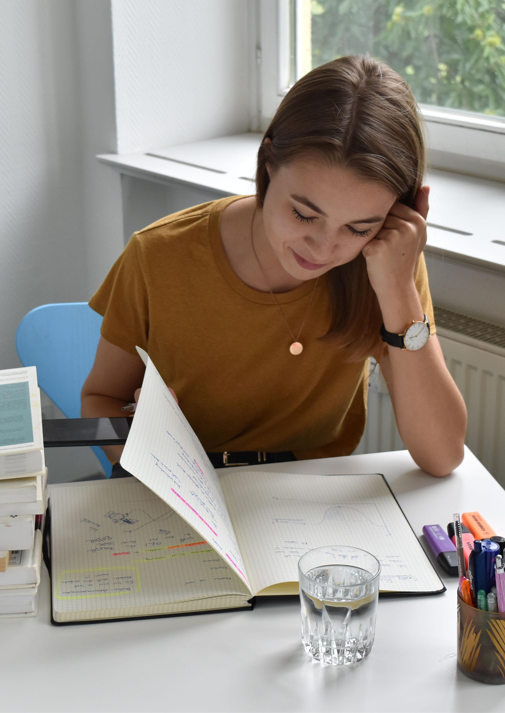 Schülerin sitzt an einem Tisch und  blättert in einem Übungsbuch
