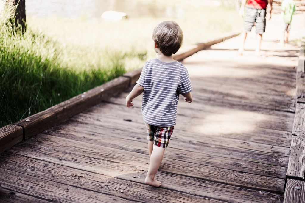 A child walks on a wooden boardwalk. During the toddler years, children show greater interest in exploring their world. Photo courtesy of Japheth Mast via Unsplash.
