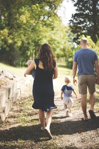 A family takes a stroll outside in a wooded park space on a bright summer day. Their faces are turned away from the camera.