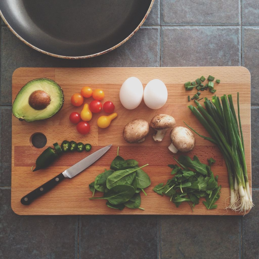 Vegetables, including spinach, avocado, grape tomatoes, mushrooms and scallions--are arranged with two eggs on a wooden cutting board with a kitchen knife on top of a backdrop of grey tiles. A cooking pan lies partially across the top of the photo.