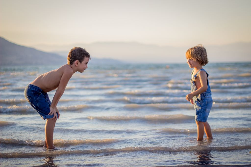 Two siblings play together by the shore at sunset.