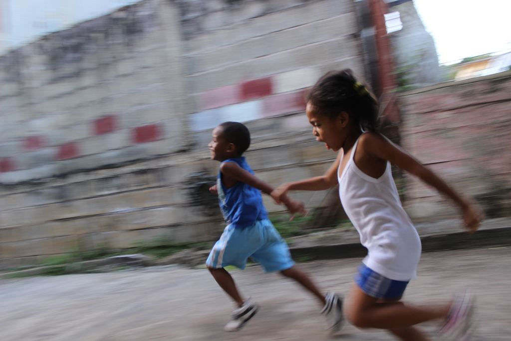 Two siblings run together in a city street. They are holding hands.