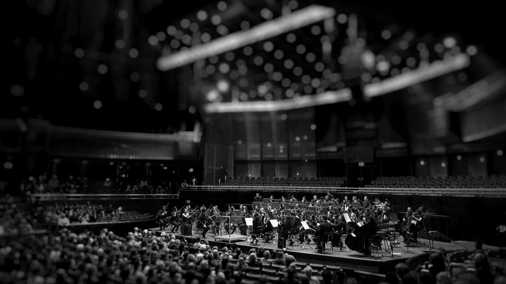 An orchestra plays for a packed assembly hall.