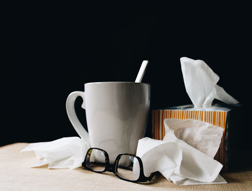 A white ceramic cup with a metal spoon, a paper box of tissues and a pair of upside-down glasses imply it's flu time in this household.