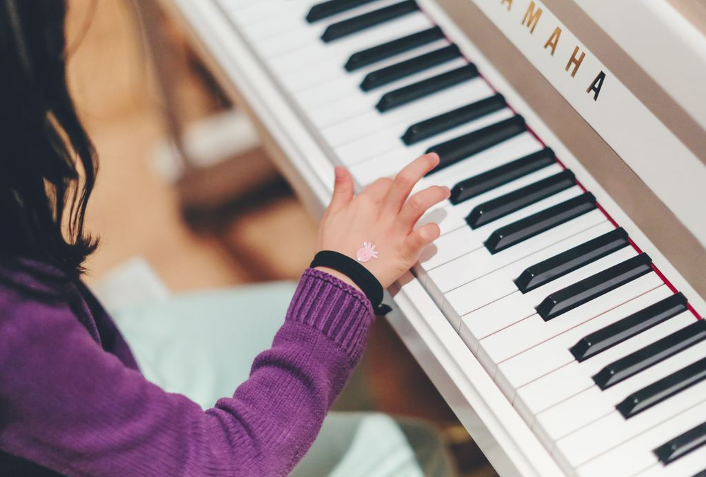A child practices piano skills while sitting at a Yamaha.