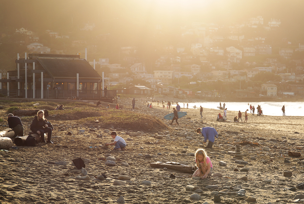 People enjoying the beach sand during sunset