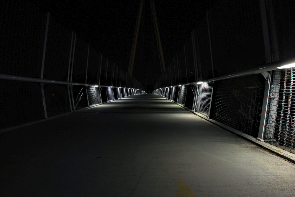 Lit pedestrian bridge at night Cupertino, CA