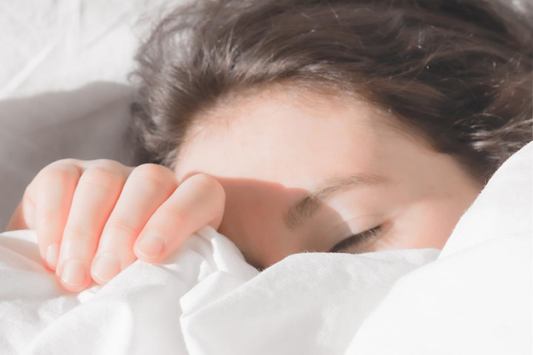 Frau deckt ihr Gesicht mit einer weißen Bettdecke zu