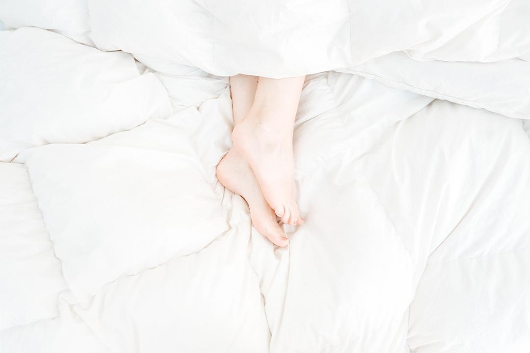 Füße, die aus einer weißen Bettdecke rausgucken