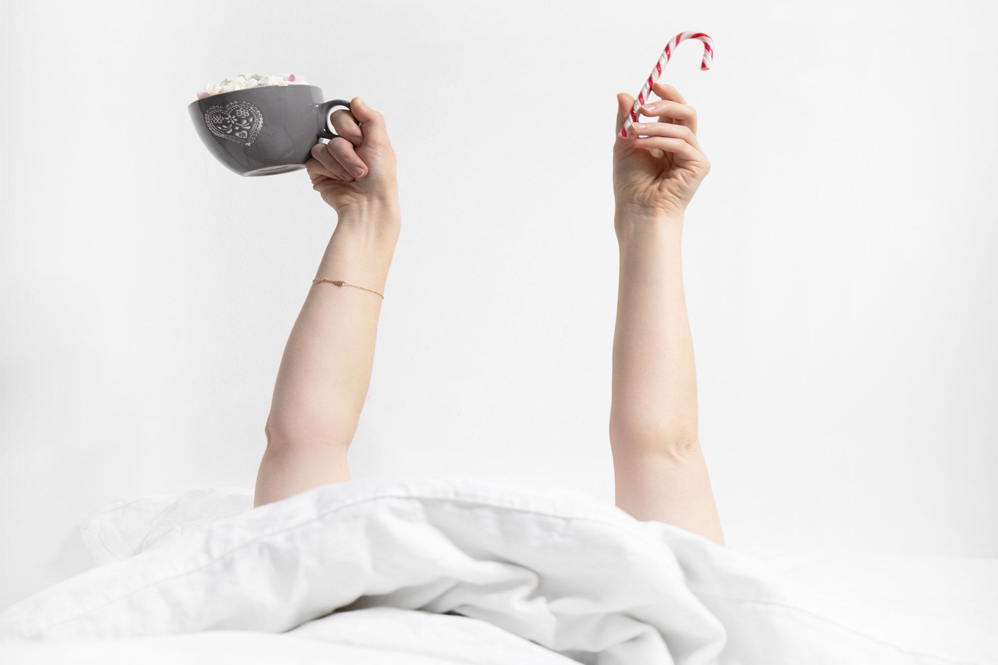 hochgehaltene Hände mit einer Tasse und Zuckerstange