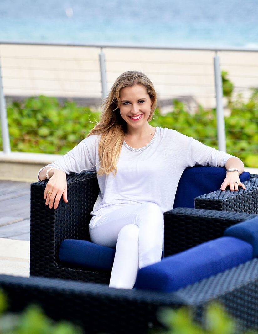 Andrea sitting in a sofa chair near a beach