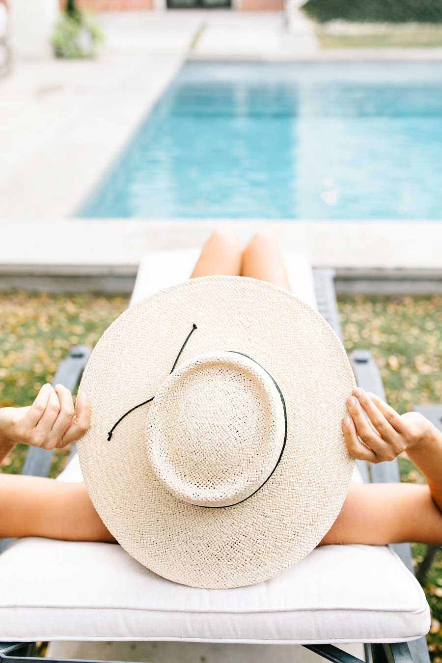 Woman relaxing on a lounge at a resort pool