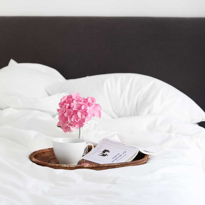 platter with a cup of coffee and a flower on a resort bed