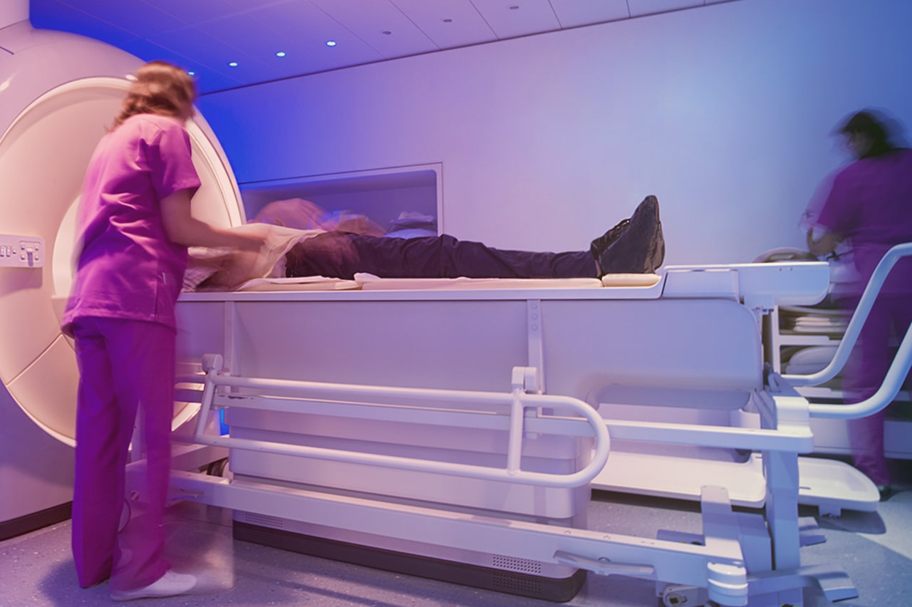 mri technician positions patient into mri machine