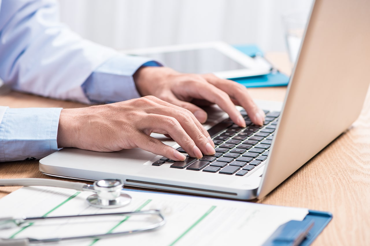 A physician types on a laptop