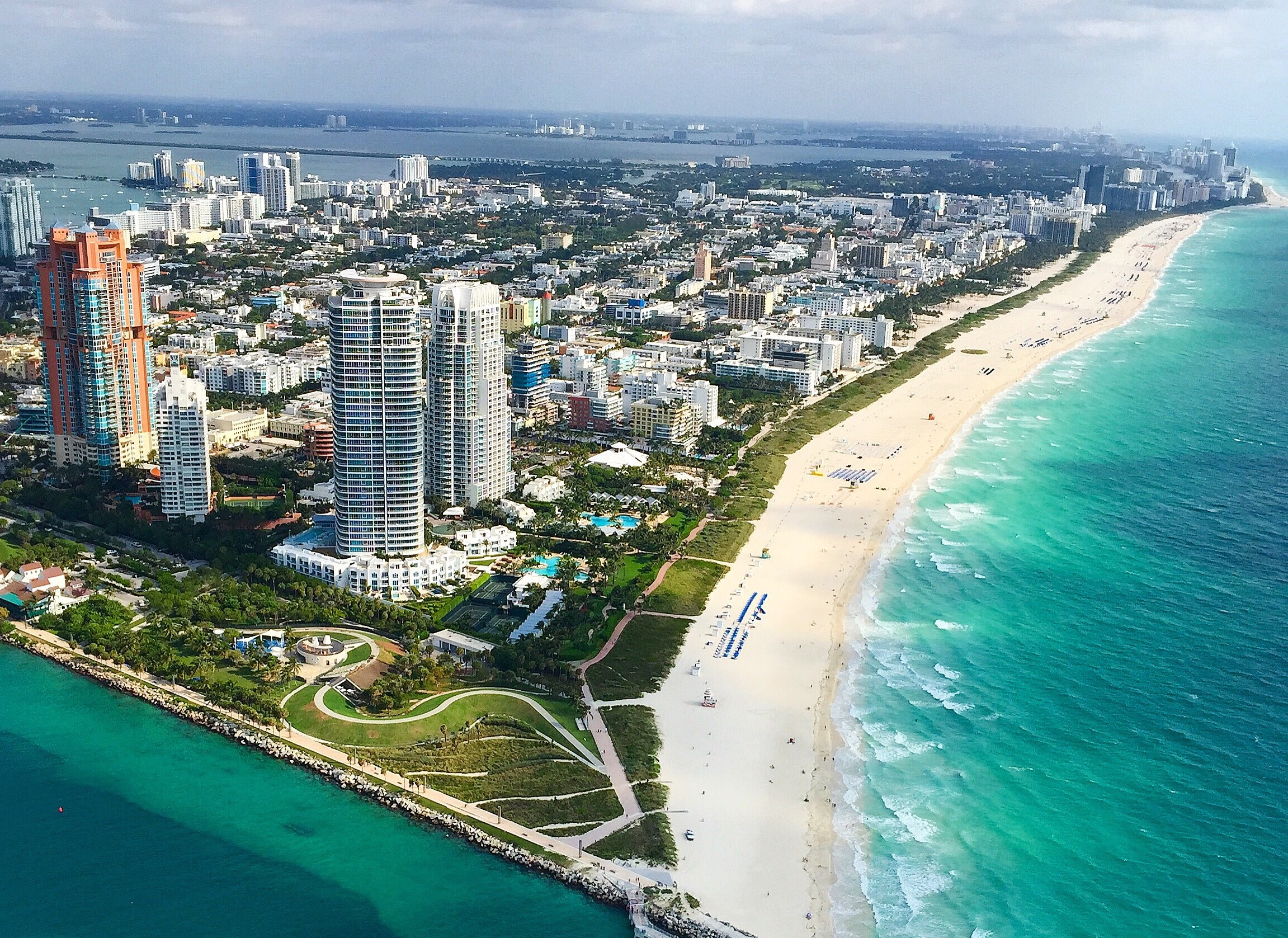 Aerial view of Miami, FL with buildings and green waterfront.