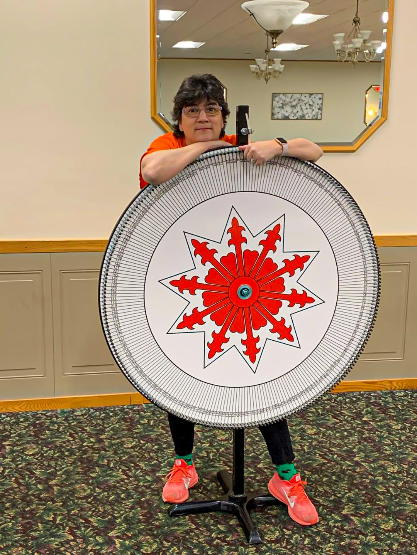 Woman standing behind meat raffle wheel