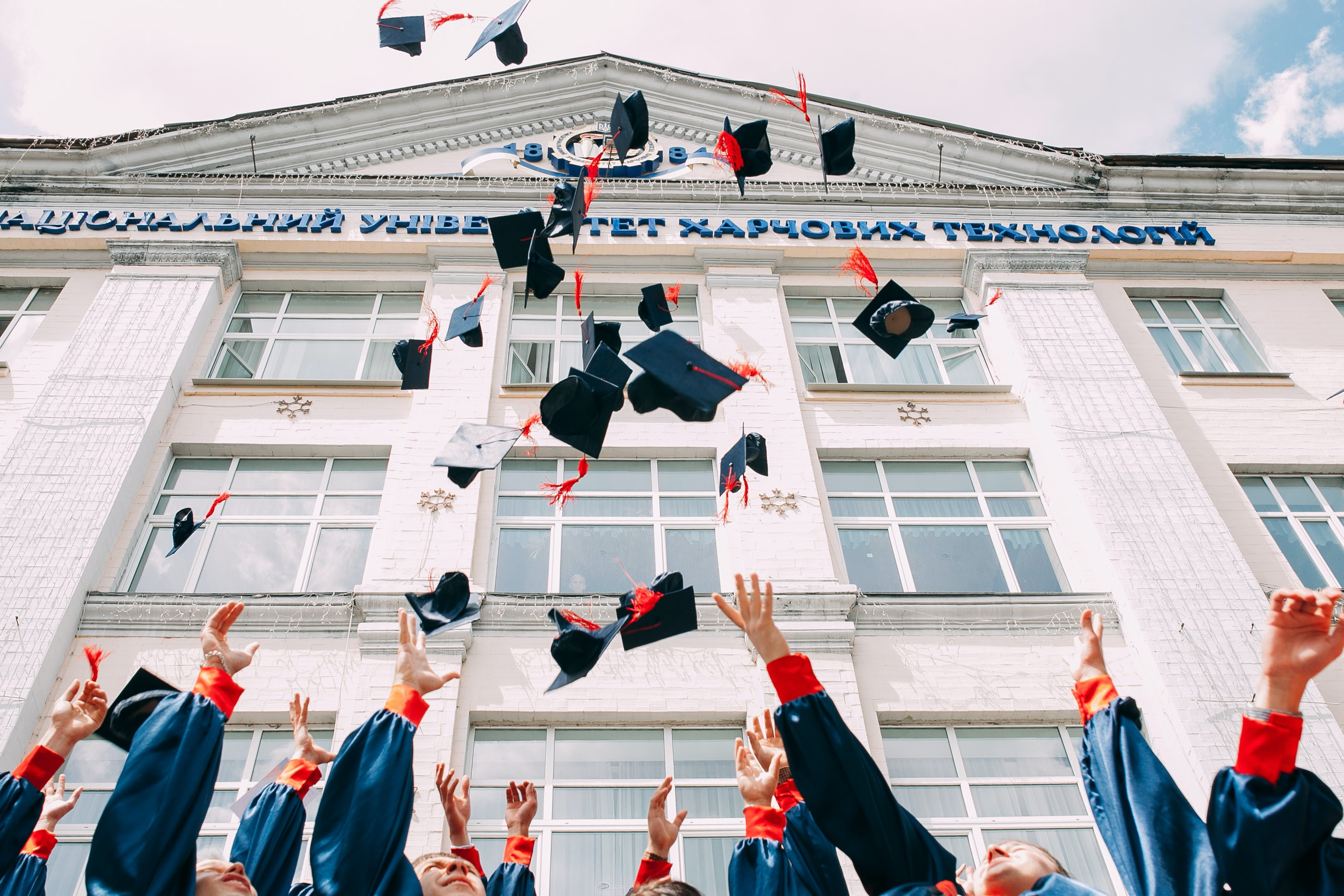 University Students Throwing Hats In Air