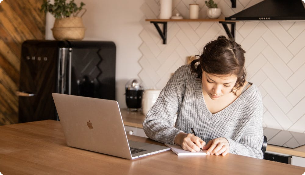 Woman taking notes during Virtual Interview