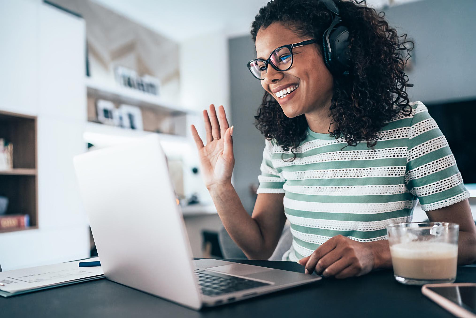 Woman presenting webinar in front of laptop