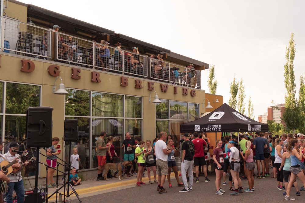 People gather outside of Bridger Brewing in Bozeman to enjoy a beer after a community 5k run