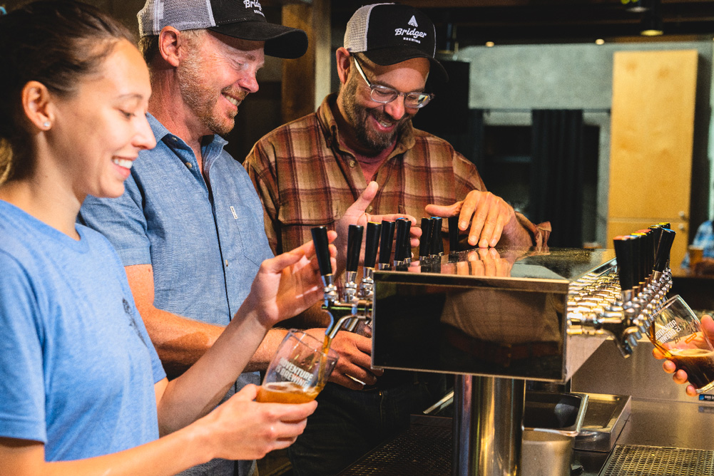 Three Bridger employees smiling and filling beer pints at the brewery