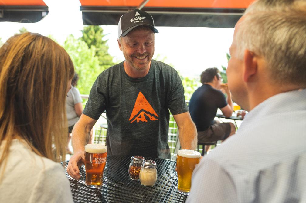 Bridger owner serving beer to guests outside at Bridger Brewing in Bozeman