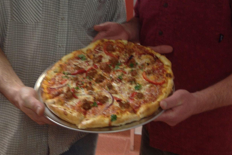 One of the owners and staff holding up the first pizza ever made by Bridger